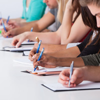 Cropped image of university students writing at desk in classroom